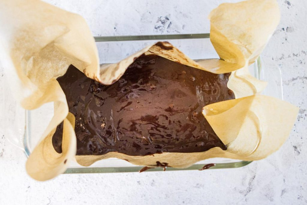 brownie batter in a loaf pan with parchment paper