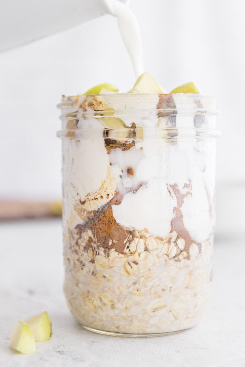 pouring milk into a glass jar of overnight oats