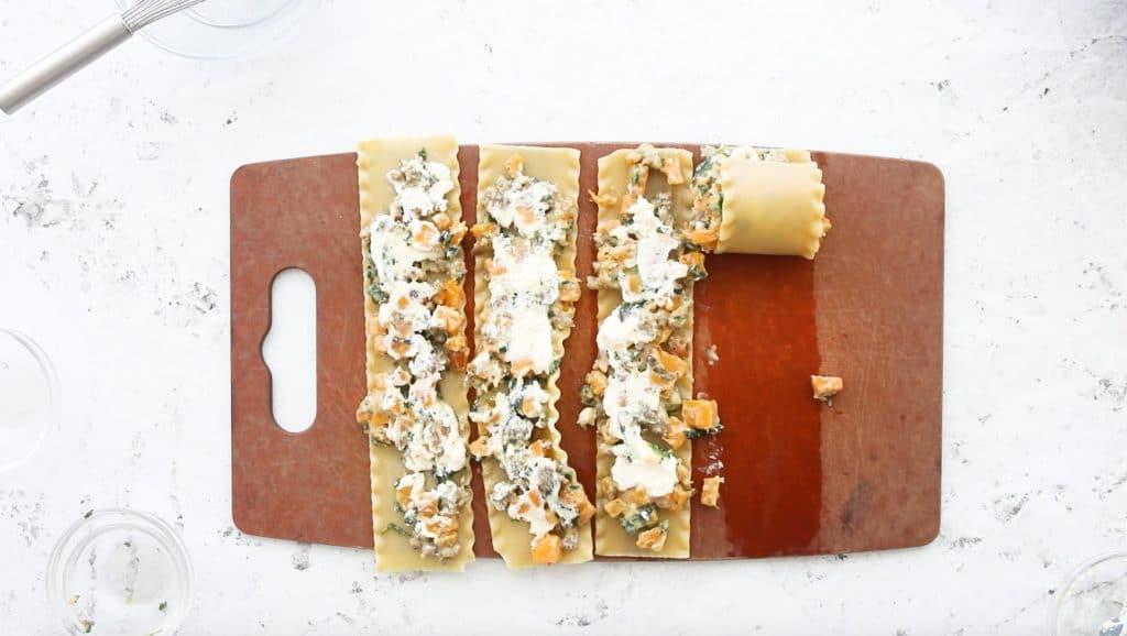 four butternut squash lasagna rolls on a cutting board