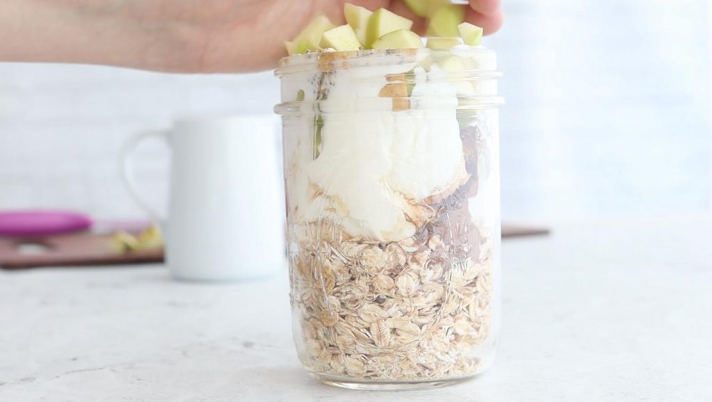 hand adding apples to a jar of overnight oats