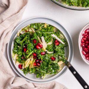 kale, apple, and pomegranate salad with fork in it