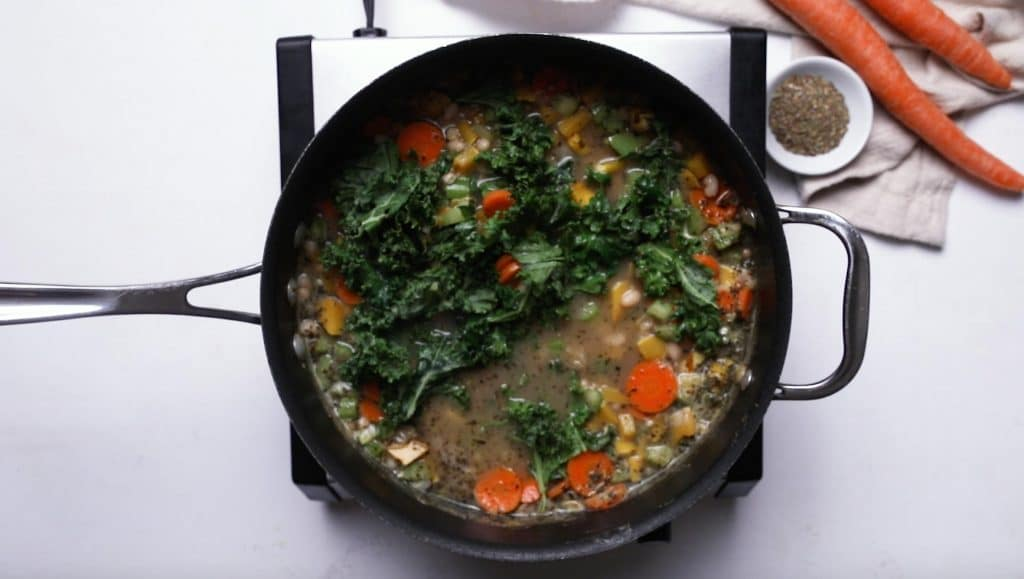 vegetable soup with kale in a large black saucepan