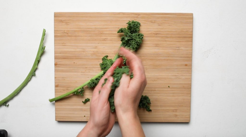 hands massaging kale over a cutting board