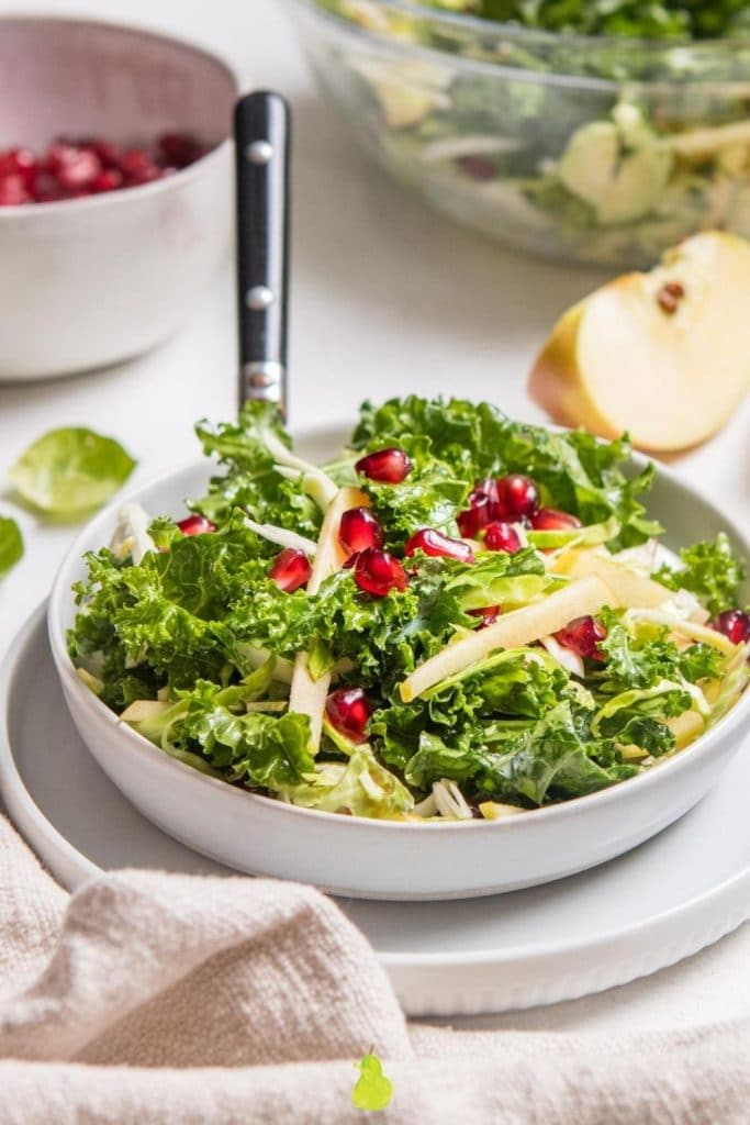 kale salad with pomegranates in white bow with ingredients behind it