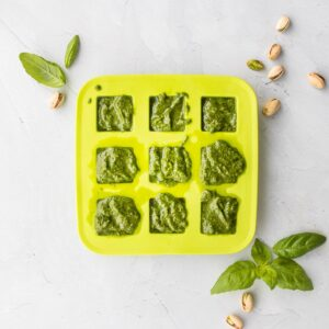 pistachio pesto in a green ice tray with ingredients around it
