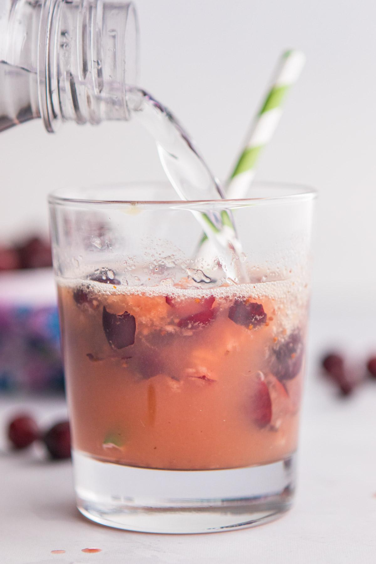 pouring sparkling water into cranberries in a glass
