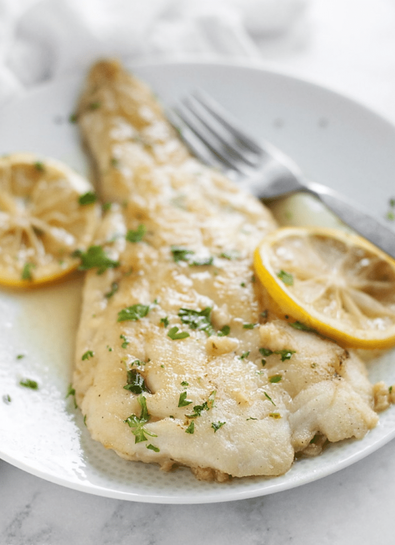 filet of white fish with herbs and lemon slices on a plate