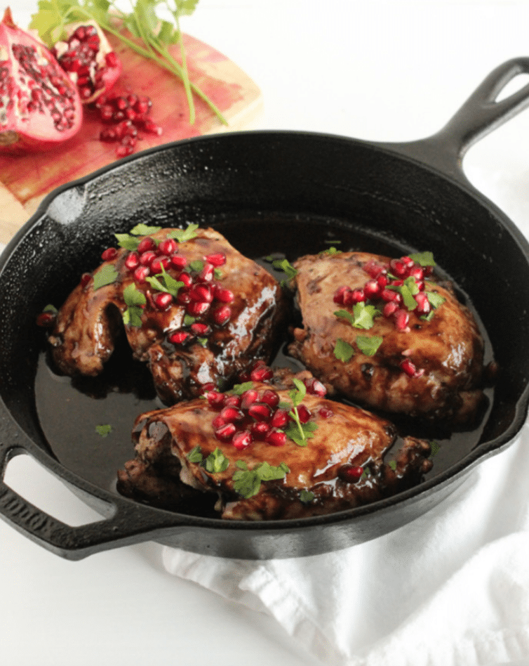 three chicken thighs with pomegranates in a cast iron skillet