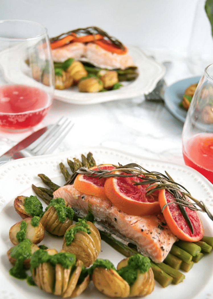 salmon over asparagus with blood oranges on top with hassleback potatoes with pesto next to it on a plate