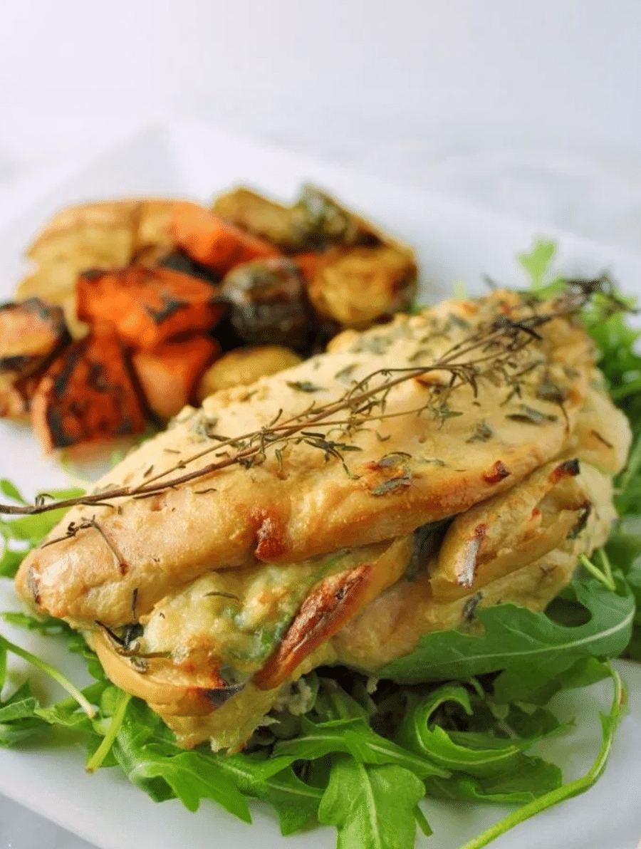 stuffed chicken over a bed of lettuce with vegetables next to it