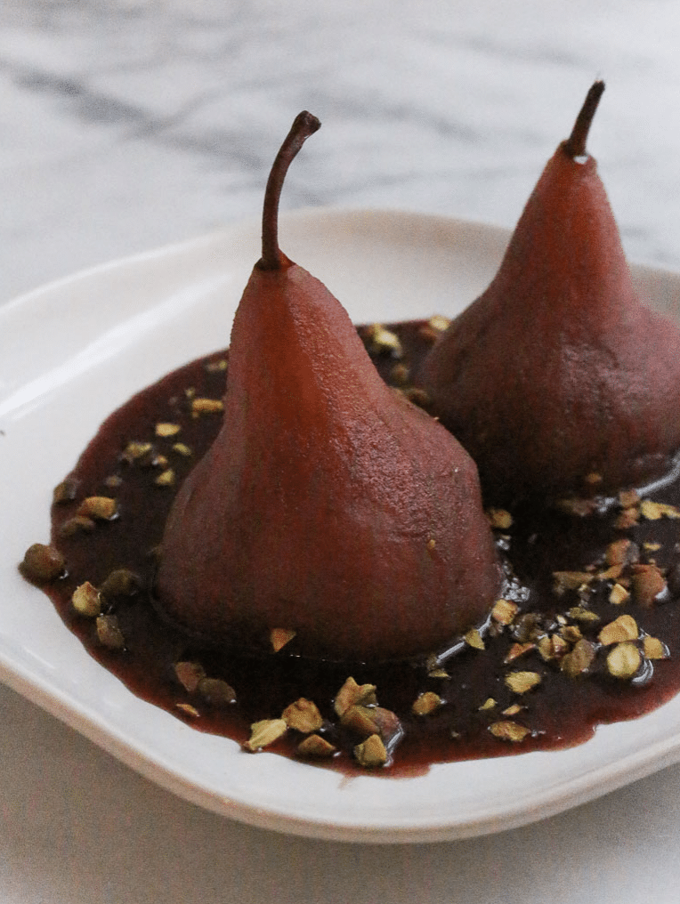 two wine poached pears on a plate