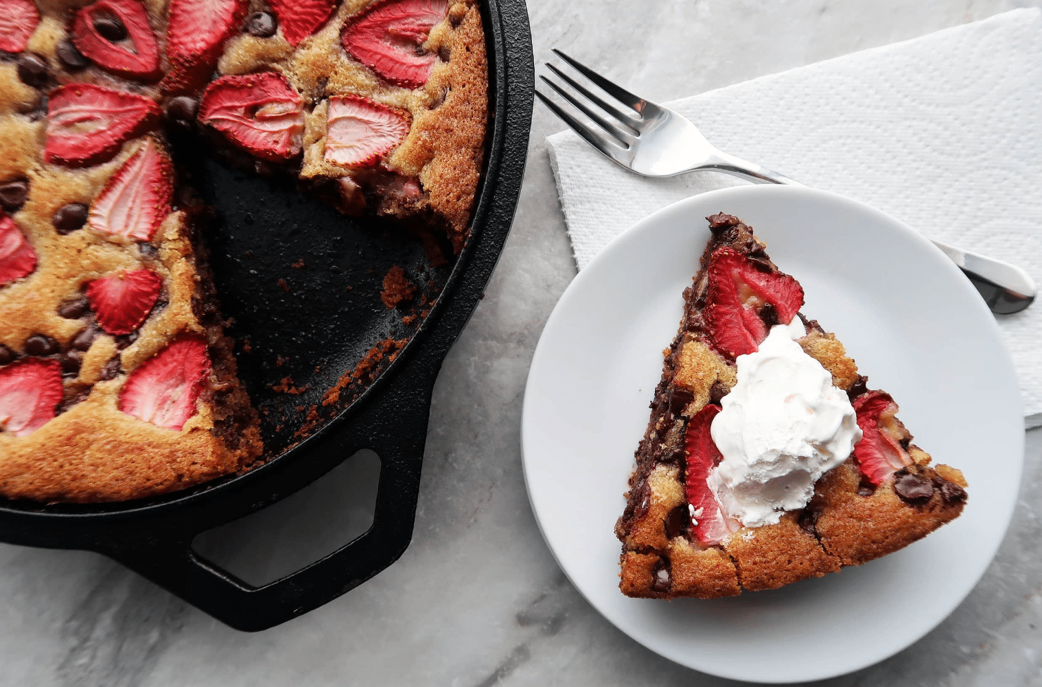 slice of chocolate chip strawberry skillet cookie on a plate next to cake in a skillet