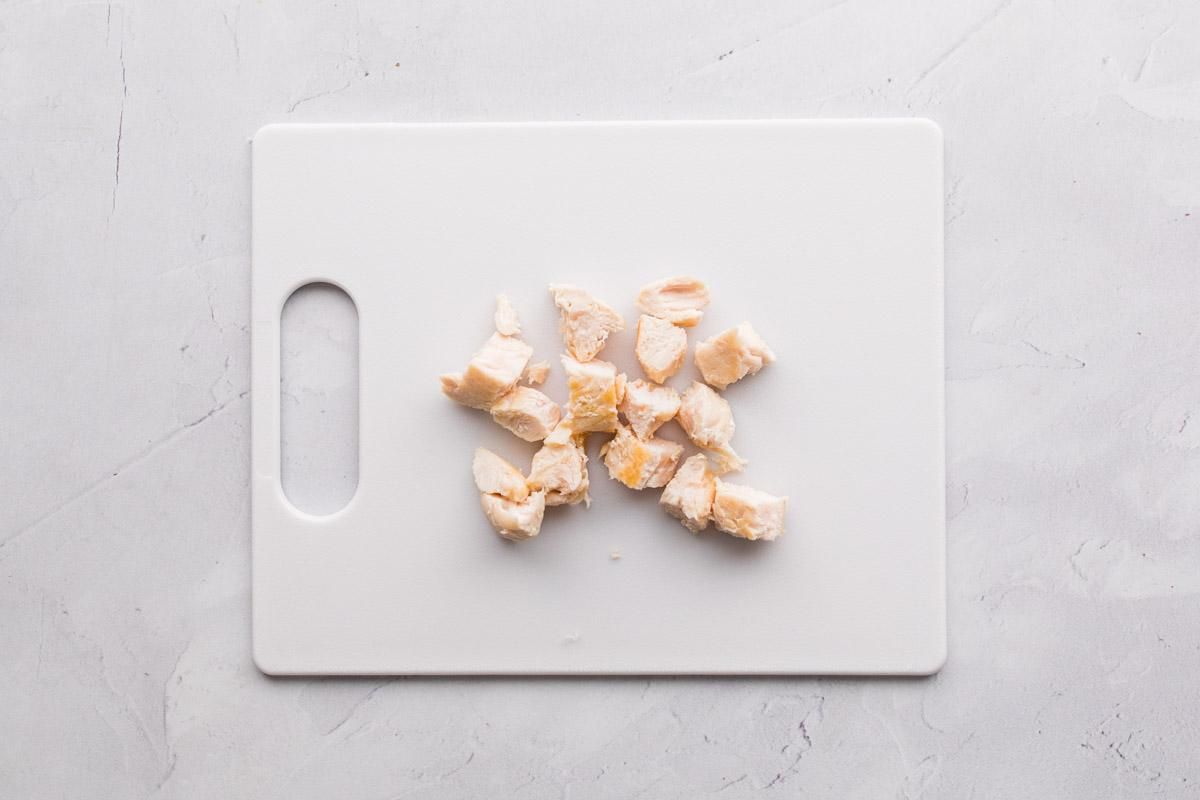 chopped cooked chicken on a white cutting board