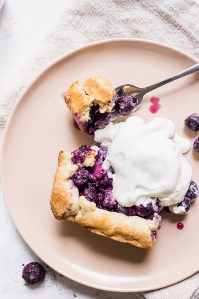 slice of blueberry pie with cream on a pink plate