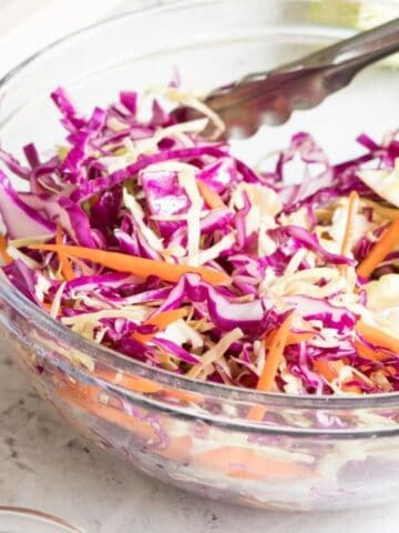 glass bowl of red and green cabbage and shredded carrots