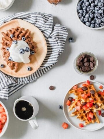 waffles and toppings on plates and in bowls on a table