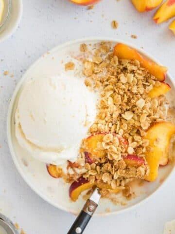 peach crisp with vanilla ice cream on a plate