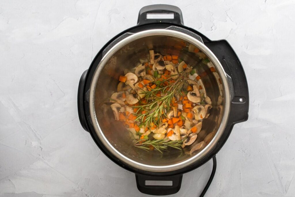 vegetables and rosemary sprigs in an Instant Pot