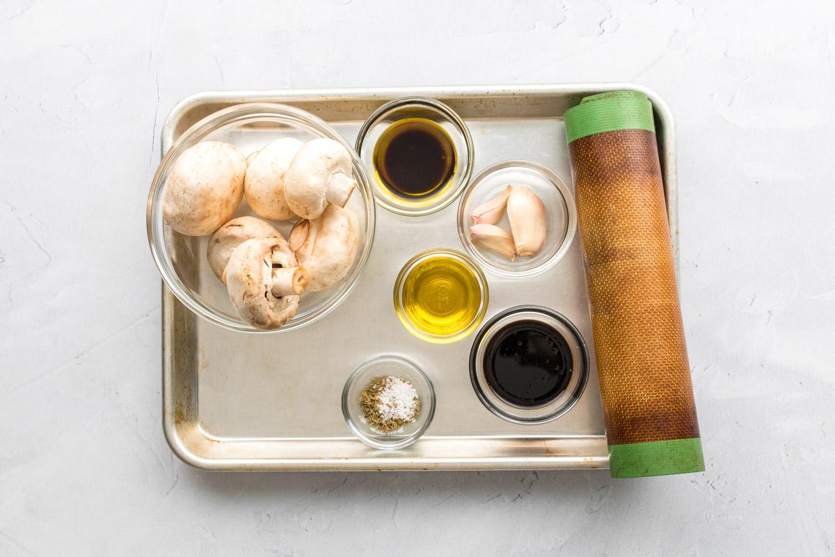 ingredients for garlic roasted mushrooms on a baking sheet
