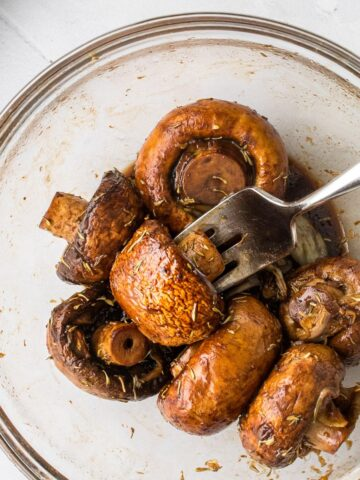 fork in a balsamic roasted mushroom in a bowl