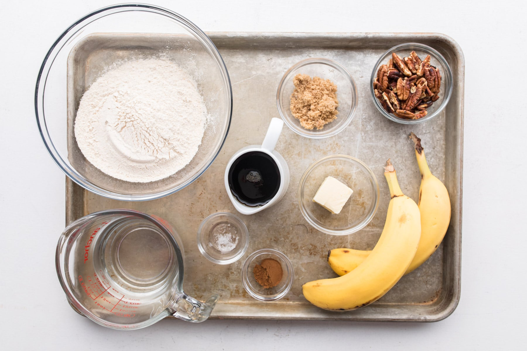 bananas, sugar, pancake mix, syrup, and other ingredients on a baking sheet