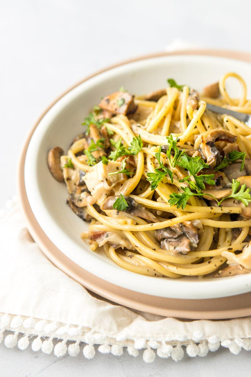 chicken bacon mushroom pasta on a white plate with parsley