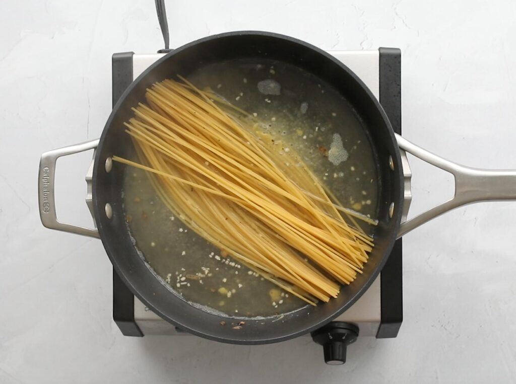 pasta cooking in a large frying pan