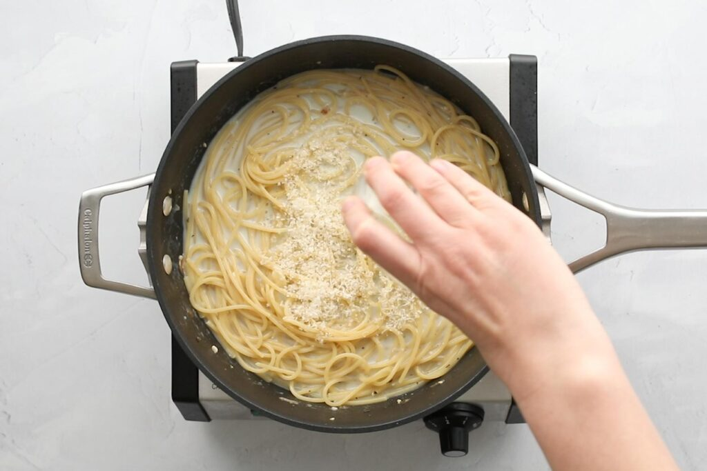 sprinkling parmesan cheese over pasta in a frying pan