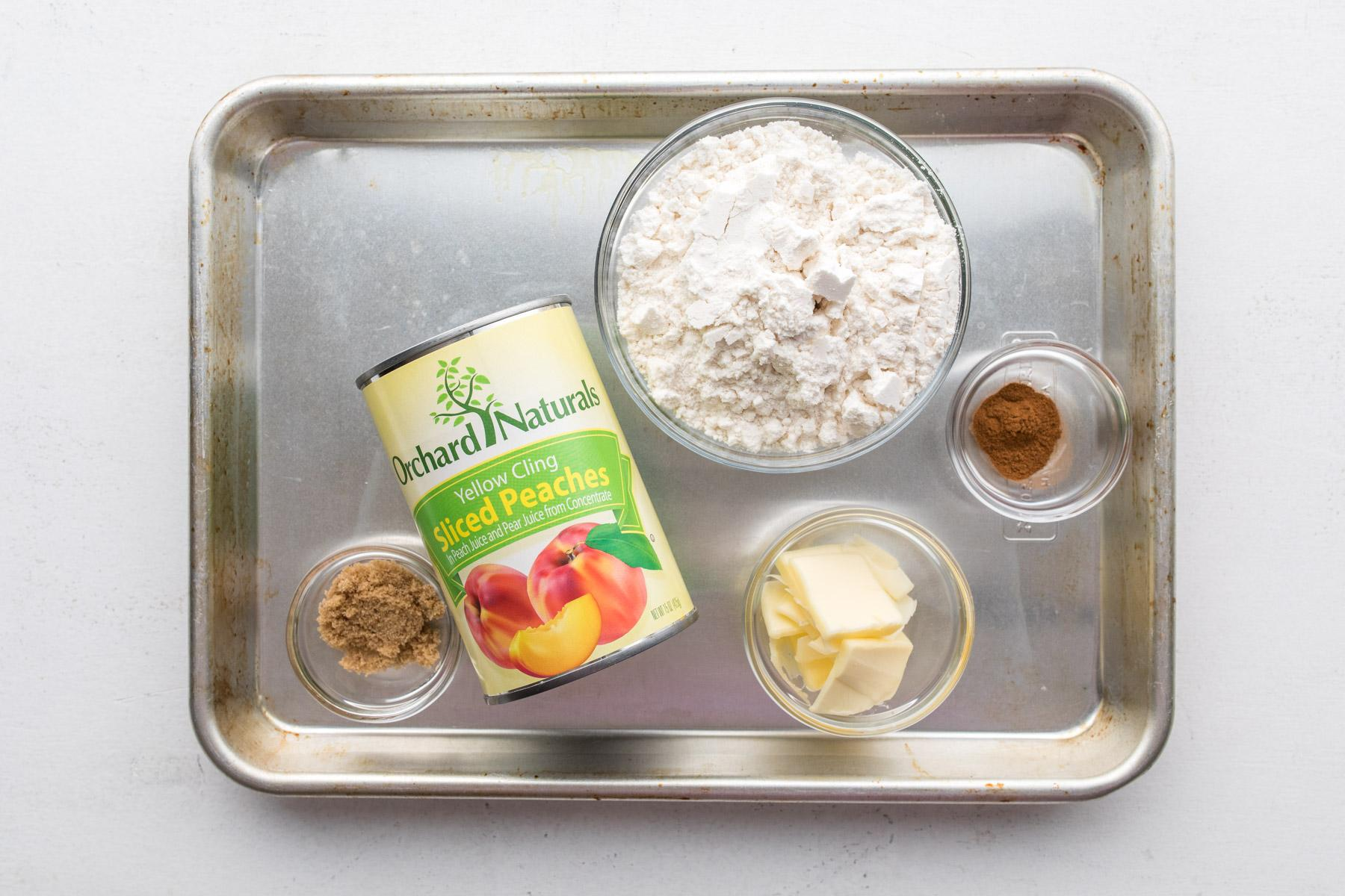 can of peaches, flour, butter, and spices on a cookie sheet