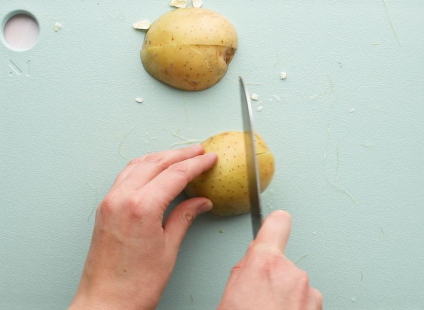 cutting yukon gold potato half on a green cutting board