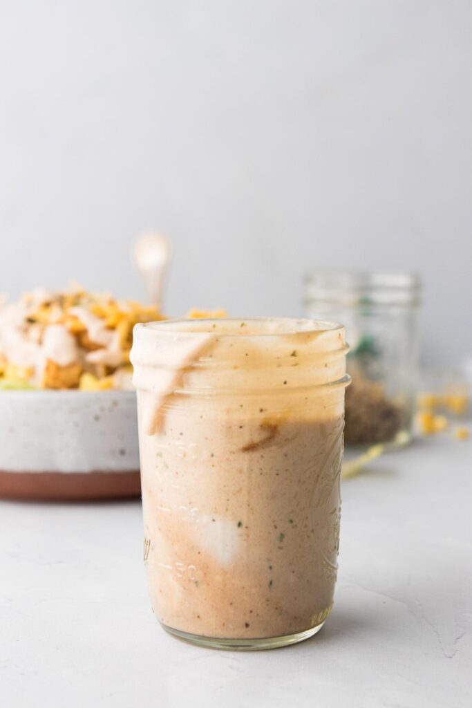 BBQ ranch dressing in a jar with salad in the background