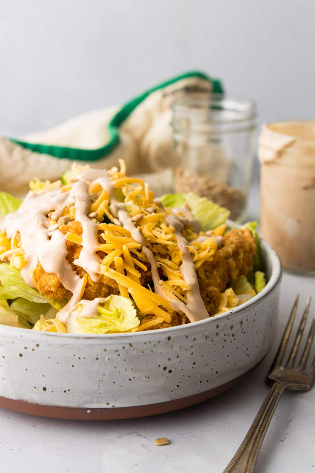 chicken, shredded cheese, and vegetable salad in a grey bowl