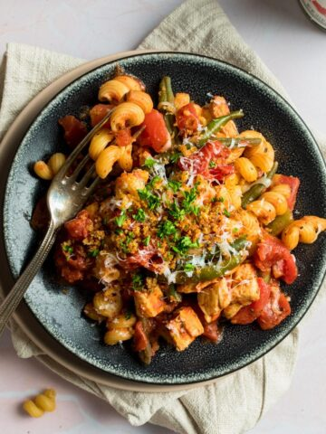 square photo of spiral pasta with tomatoes on a black plate with a fork