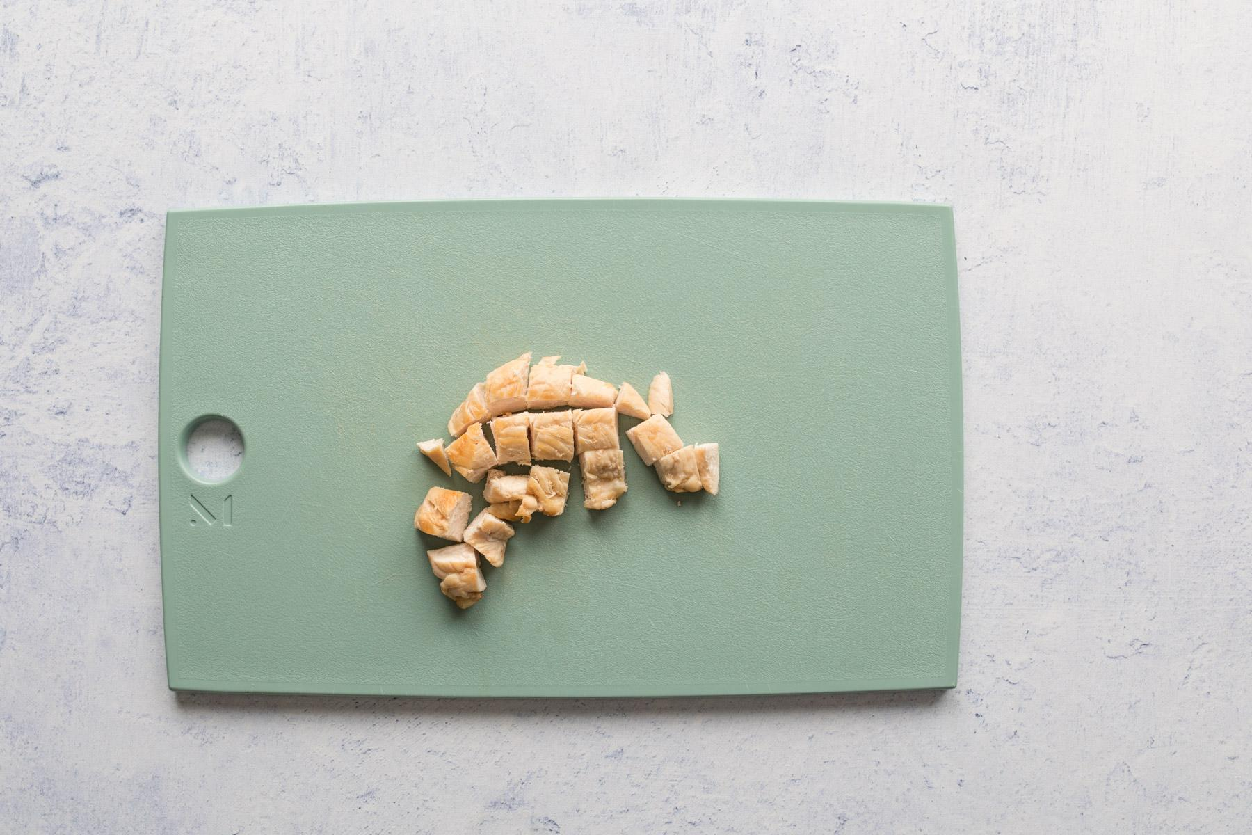chopped chicken on a green cutting board