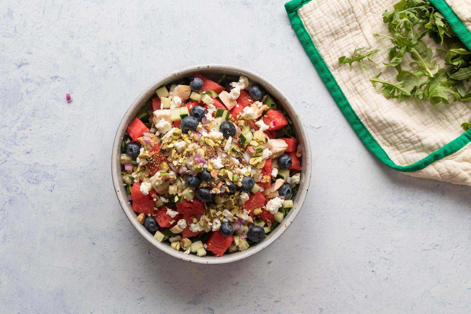 bowl of watermelon, feta, blueberries and other salad ingredients