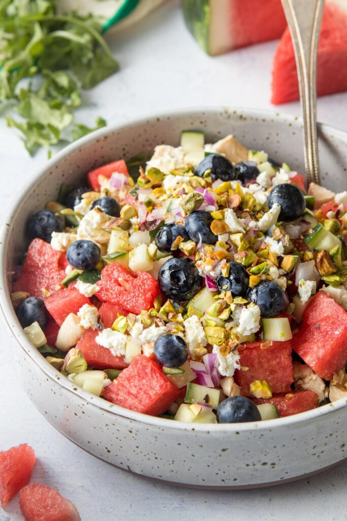 close up of watermelon, feta cheese, and blueberries in a large bowl