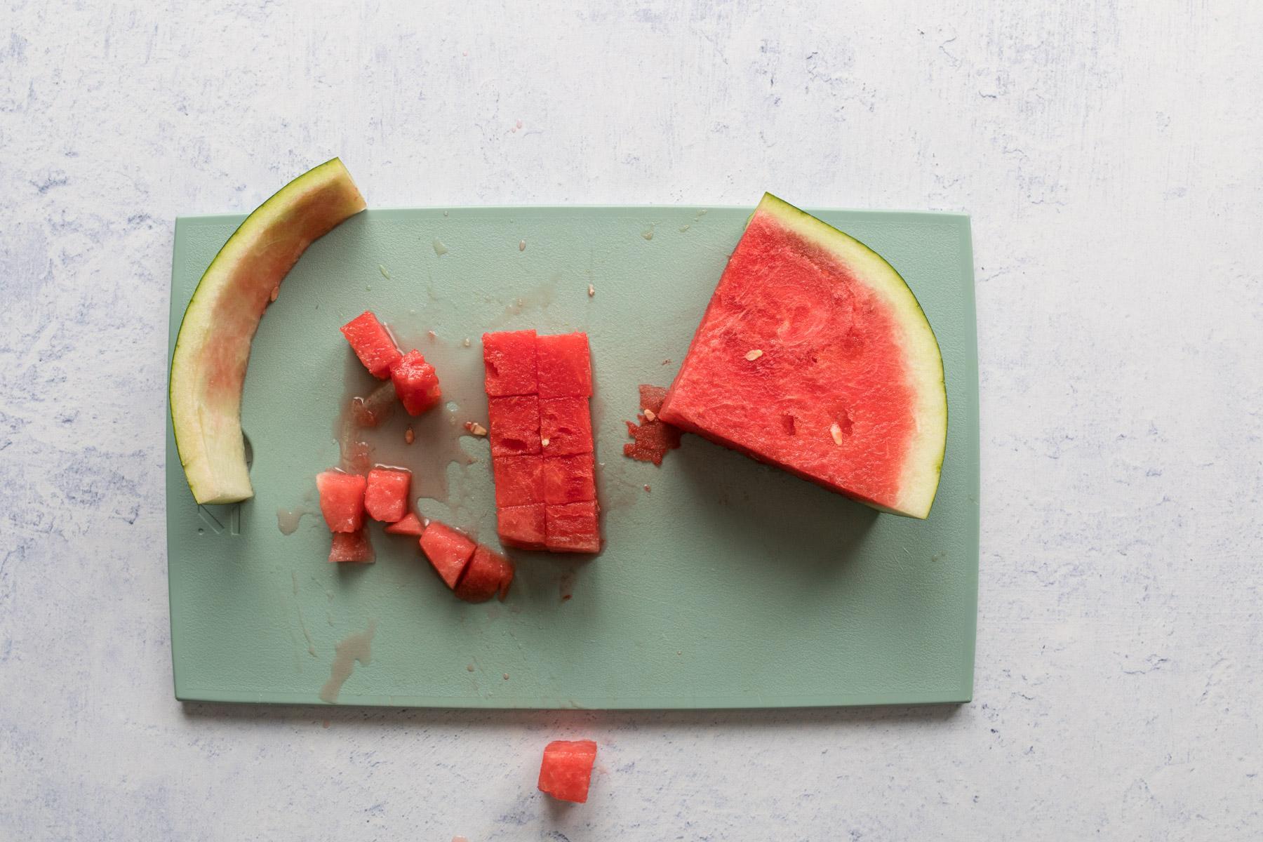 cut watermelon on a green cutting board