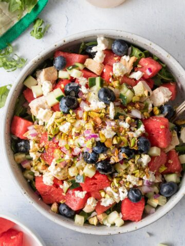 large bowl full of watermelon, blueberries, feta cheese on a table
