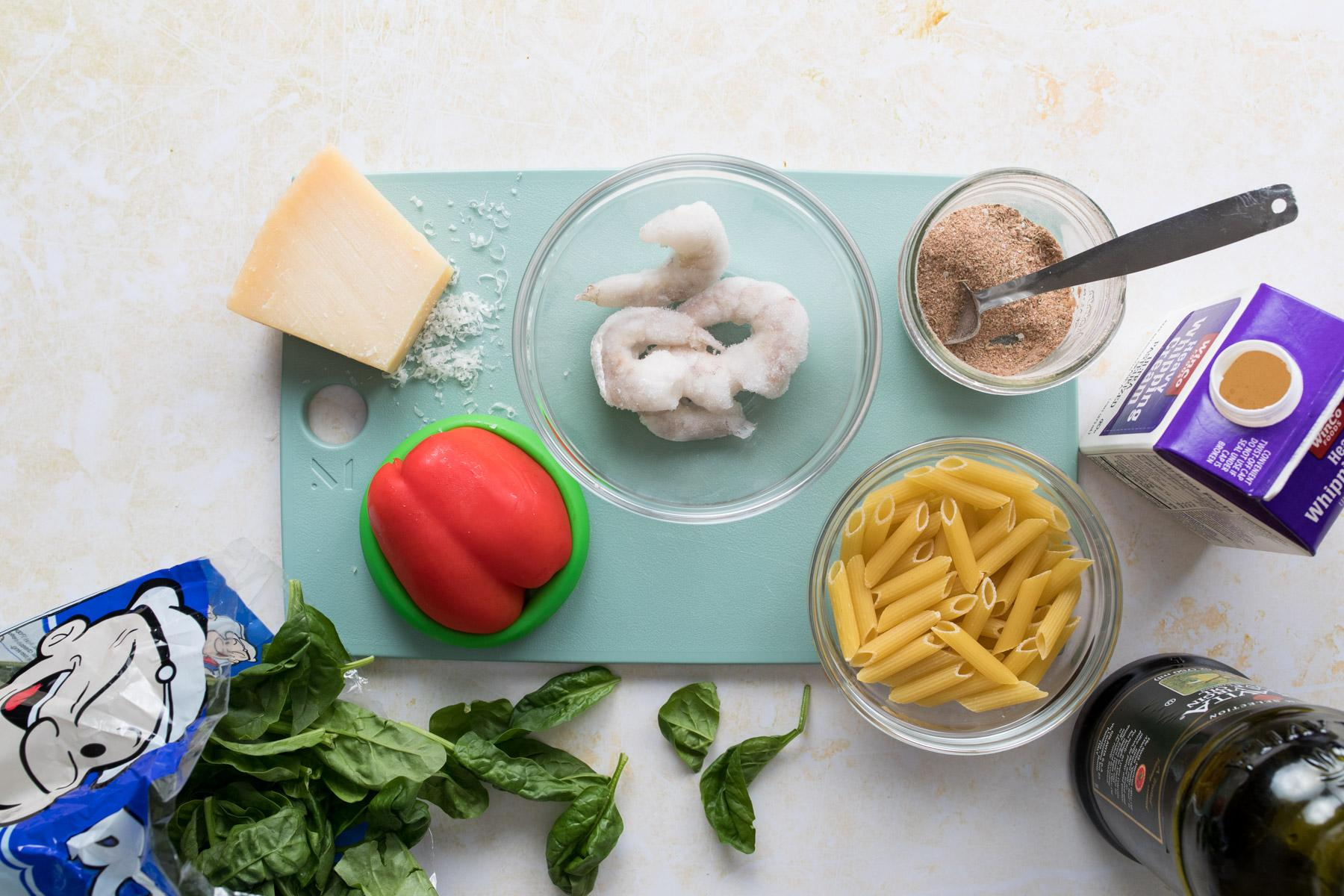 cutting board with bowls of ingredients for jerk shrimp pasta