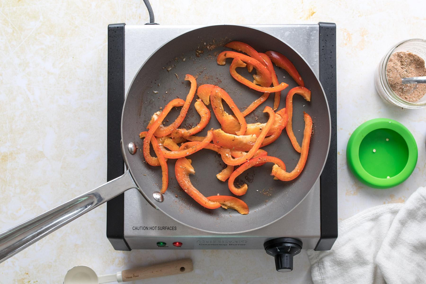 sliced red bell peppers in a sautee pan