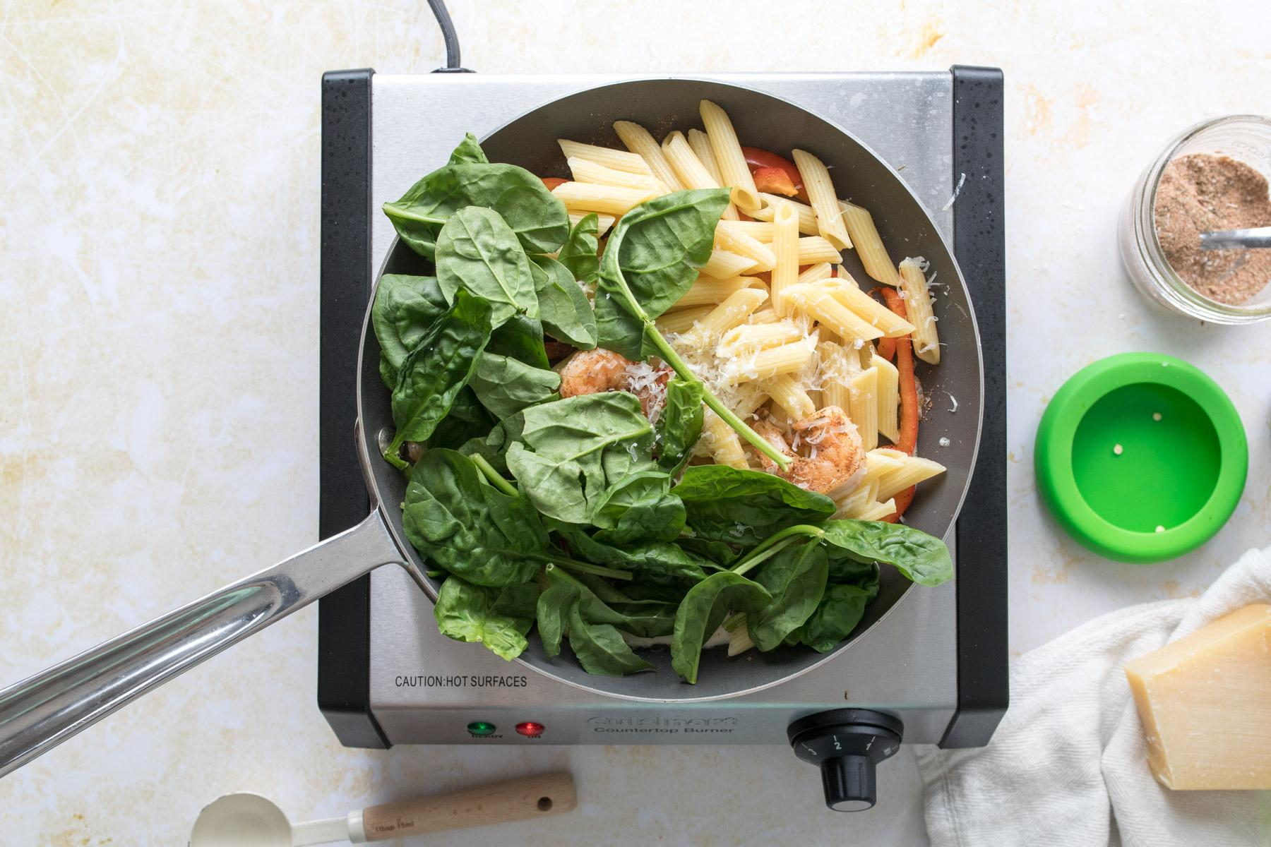spinach, pasta, shrimp, and bell peppers in a skillet