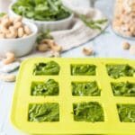 Green ice tray full of pesto on a table