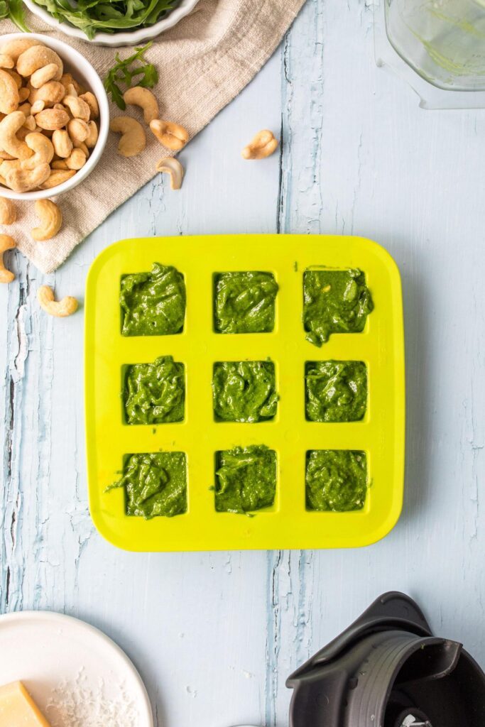 pesto in a green ice tray with ingredients around it