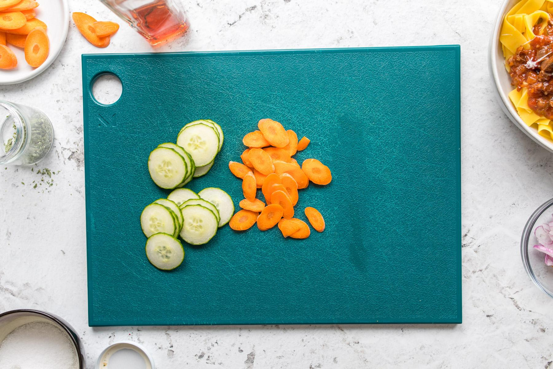 sliced cucumber and carrot on a green cutting board